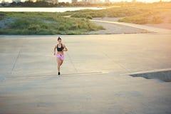 Atletische vrouwelijke agent die over lange afstand uit aanstoten stock foto
