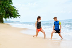 atletismo Allungamento adatto delle coppie, esercitantesi sulla spiaggia Sport, F Fotografia Stock Libera da Diritti