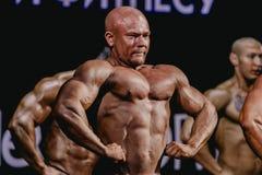 Atlety bodybuilder w pozie stawia czoło naprzód, cedzący klatkę piersiową i prasy Fotografia Stock