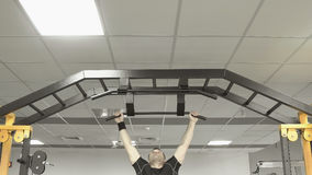 Atlety mięśniowej sprawności fizycznej męski ciągnąć up na horyzontalnym barze w gym Obrazy Royalty Free
