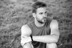Atlety odzieży krokomierza bransoletka na ręce Sportowy mężczyzna relaksuje na zielonej trawie Sprawdzać treningów rezultaty Tech zdjęcia stock