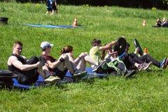 atlety wykonuje zadanie przelewanie ciężary each inny w siedzącej pozyci Zdjęcia Royalty Free