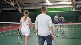 Atlety z uśmiechem gratulują each inny z dobrą grze gracz w tenisa radośnie potrząśnięcie która przychodził końcówka, zbiory