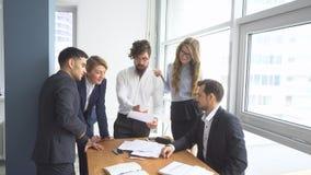 Atmósfera de funcionamiento en la oficina empleados para ver documentos en el lugar de trabajo Grupo de hombres de negocios de la imagen de archivo
