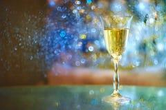 Atmósfera festiva por la tarde con un vidrio de luces de oro del champán y de un arco iris Fotografía de archivo