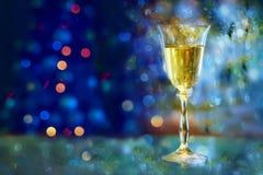 Atmósfera festiva por la tarde con un vidrio de luces de oro del champán y de un arco iris Imagenes de archivo
