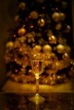 Atmósfera festiva por la tarde con un vidrio de luces de oro del champán y de un arco iris Foto de archivo
