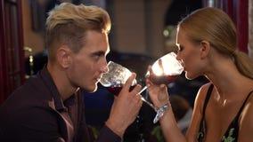 Atmósfera romántica alrededor del vino de consumición bonito del hombre y de la mujer en el restaurante y mirada de uno a con la  almacen de metraje de vídeo