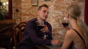 Atmósfera romántica alrededor del vino de consumición bonito del hombre y de la mujer en el restaurante y mirada de uno a con la  almacen de video