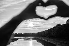 Atmósfera romántica de la luz del sol de la puesta del sol Gesto del corazón delante de la puesta del sol sobre el río Manos en s imágenes de archivo libres de regalías