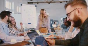 Atmósfera sana del lugar de trabajo Mujer de negocios sonriente positiva feliz que habla con los empleados multiétnicos en la reu almacen de metraje de vídeo