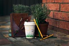 Atmósfera típica del inconformista: Taza de café con los lápices, el cuaderno y las plantas Foto de archivo