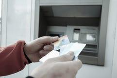 ATM机器的人有藏匿处的信用和转账卡 免版税库存图片