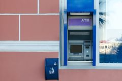 ATM в стене здания около окна, около его малый мусорный бак и проверки Стоковое Изображение RF