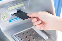 Закройте вверх по руке вводя карточку в ATM стоковые изображения