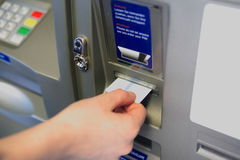 ATM Access. Female hand inserts banking card