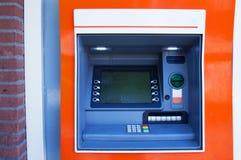 ATM machine. Orange ATM banking machine for withdraw money Royalty Free Stock Photos