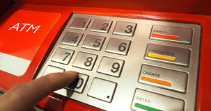 ATM machine red color and finger hand close-up. ATM machine red color and finger hand touch on number button for withdrawal and close-up shot Royalty Free Stock Photo