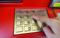 ATM machine red color and finger hand close-up. ATM machine red color and finger hand touch on number button for withdrawal and close-up shot Royalty Free Stock Photography