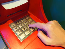 ATM machine red color and finger hand close-up. ATM machine red color and finger hand touch on number button for withdrawal and close-up shot Royalty Free Stock Images