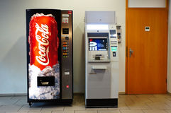 ATM and vending machine. Coca Cola vending machine and a ATM standing in a shopping mall in Poznan, Poland Royalty Free Stock Photos