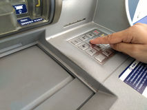 ATM for withdraw your money. Hand entering PIN numbers on ATM Stock Photos