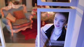 Atmosfären av väntande på jul En ung härlig kvinna ser ut fönstret till gatan stock video