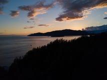 Atmosfärisk fyr på klippan nära havet medan solnedgång arkivfoton