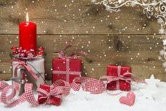 Atmosfärisk julkort med den röda bränningstearinljuset och gåvor arkivbilder