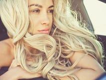 Atmosfärisk stående av den härliga blondinen i bil royaltyfri bild