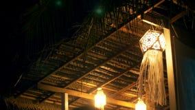 Atmosfäriskt bakgrundsskott av härliga radljus på nattterrassen, traditionell pappers- lykta som vinkar i vinden arkivfilmer