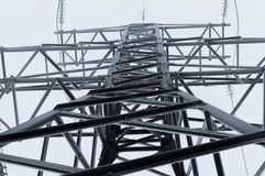Atmosfäriskt foto för Closeup av det höga spänningsöverföringstornet som täckas med rimfrostanseende på den gråa himlen Royaltyfri Foto
