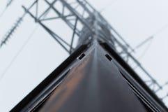 Atmosfäriskt foto för Closeup av det höga spänningsöverföringstornet som täckas med rimfrostanseende på den gråa himlen Arkivfoto
