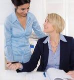 Atmosfera amichevole sul lavoro: donna di affari sorridente due immagine stock