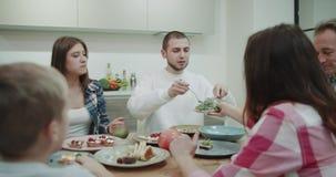 Atmosfera bonita da família na tabela de jantar que corta o alimento e que come um almoço da saúde toda junto filme