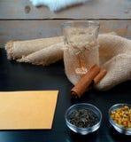 Atmosfera calda del tè con cannella, la camomilla, il gelsomino del tè verde con la candela e la tela da imballaggio a fondo di l fotografie stock libere da diritti