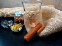 Atmosfera calda del tè con la candela e la tela da imballaggio a fondo di legno fotografia stock