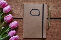 Atmosfera do caderno e da mola da pena com tulipas cor-de-rosa Fotos de Stock Royalty Free