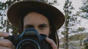 Atmosferisch close-upportret van jong mooi fotograafmeisje die met camera bij Yosemite-park langzame motie glimlachen stock videobeelden