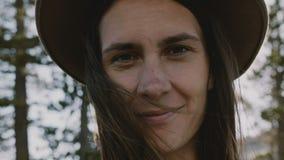Atmosferisch close-upportret van jong mooi glimlachend meisje in hoed met vliegend haar bij Yosemite-park langzame motie stock video