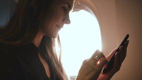 Atmosferisch die close-up van jonge gelukkige vrouw wordt geschoten die smartphone het winkelen app op de zetel van het vliegtuig stock videobeelden