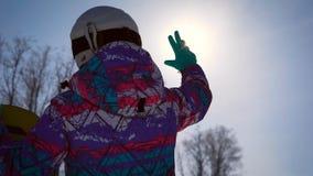 Atmosferisch kader, het concept dromen en vreugde van de dag Een snowboardermeisje vangt een heldere zon met haar hand A stock videobeelden