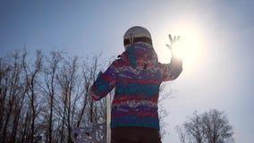 Atmosferisch kader, het concept dromen en vreugde van de dag Een snowboardermeisje vangt een heldere zon met haar hand A stock video