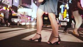 Atmosferisch langzaam motieschot van jonge vrouwelijke benen die over bezige overvolle straat bij nacht in Times Square lopen, Ne stock footage
