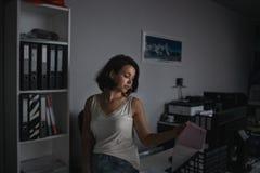 Atmosferisch portret van jonge doc. van de seductiveworkerholding bij haar werkplaats in avond Overwerkconcept royalty-vrije stock afbeelding