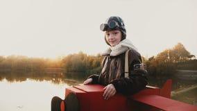 Atmosferisch portretschot van leuk meisje in proefkostuum dat van het pret retro vliegtuig camera met kalme ogen langzame motie b stock videobeelden