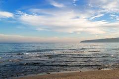 Atmosferisch zeegezicht Blauwe hemel met witte wolken over het kalme de winteroverzees in een lichte avondnevel, zachte nadruk stock afbeeldingen