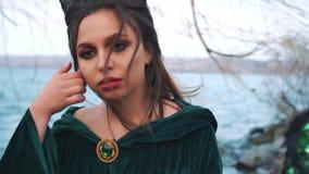 Atmosferische winderige portretfotografie van creatieve heldere samenstelling, dame in een groene smaragdgroene mantel met gouden stock footage
