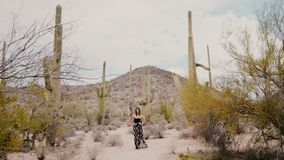 Atmosferyczny szeroki strzał, piękna młoda kobieta w smokingowym dmuchaniu w wiatrze pozuje przy epickim kaktusowym parkiem narod zbiory wideo