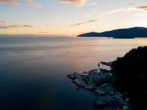Atmosphärischer Leuchtturm auf Klippe nahe Ozean während Sonnenuntergang lizenzfreie stockfotografie